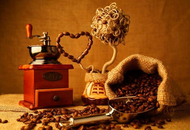 Grains de café torréfiés, moulin à café vintage sur fond de sac