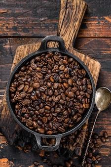 Grains de café torréfiés noirs dans une casserole sur table en bois. vue de dessus.