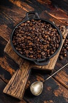 Grains de café torréfiés noirs dans une casserole