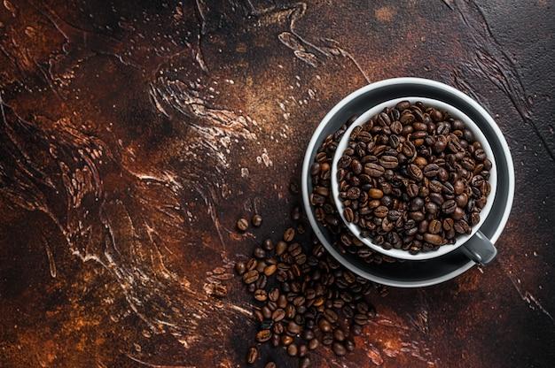 Grains de café torréfiés noirs dans une tasse sur fond noir. vue de dessus.