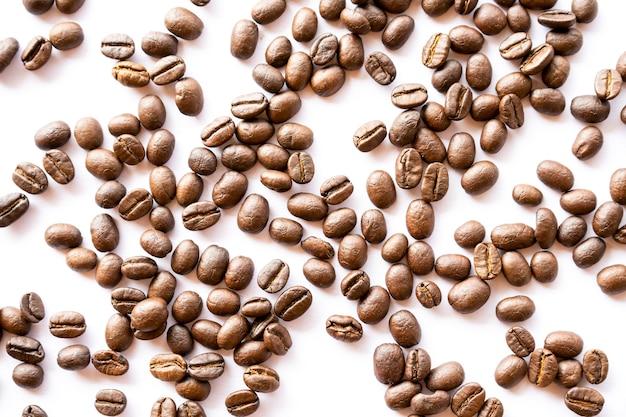 Les grains de café torréfiés organisent sur fond blanc