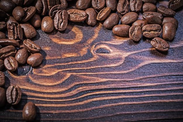 Grains de café torréfiés sur planche de bois vintage