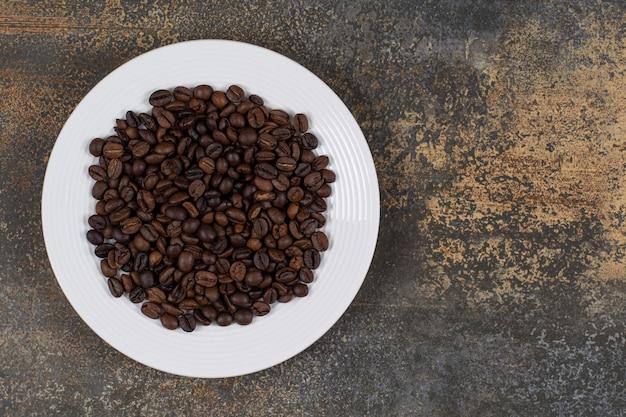 Grains de café torréfiés sur plaque blanche.