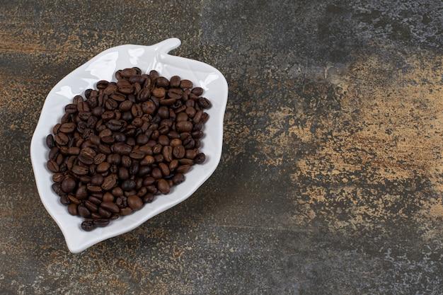 Grains de café torréfiés sur plaque en forme de feuille.