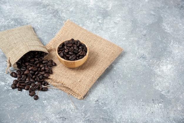Grains de café torréfiés en sac de jute et dans un bol sur marbre.