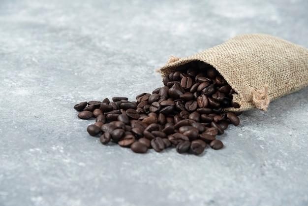Grains de café torréfiés en sac de jute sur marbre.