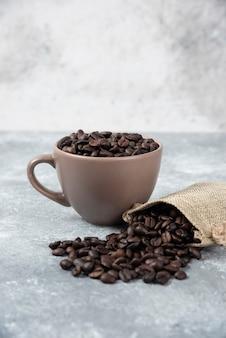 Grains de café torréfiés en sac de jute et en tasse sur marbre.
