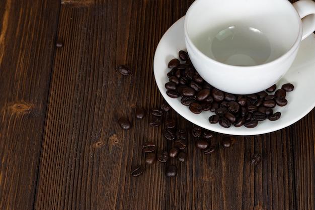 Grains de café torréfiés avec une tasse blanche sur bois