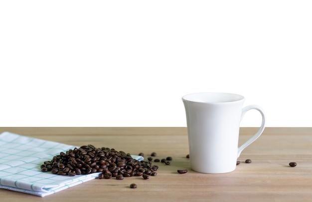 Grains de café torréfiés avec tasse de café sur bois. fond isolé.