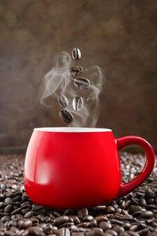 Les grains de café torréfiés tombent dans une tasse rouge d'espresso chaud. le concept d'une charge matinale de gaieté et d'énergie. vue verticale
