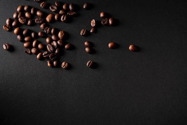 Grains de café torréfiés vue de dessus avec fond noir