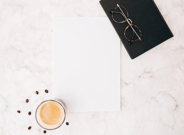 Grains de café; verre à café; papier blanc vierge; lunettes et journal sur fond de marbre texturé