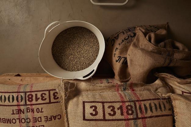 Grains de café vert cru du panier en plastique blanc