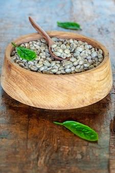 Grains de café vert non torréfiés dans un bol en bois