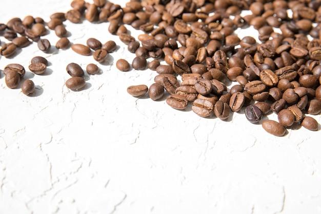 Grains de café en vrac sur blanc