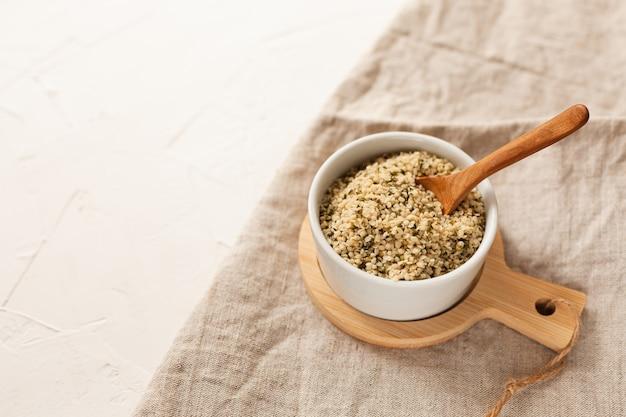 Grains de cannabis dans un bol blanc sur la table