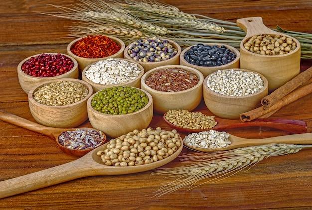 Grains de céréales, graines, haricots sur fond de bois.