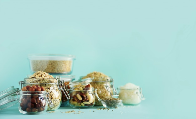 Grains, céréales, noix, fruits secs dans des bocaux en verre sur fond bleu avec espace de copie.