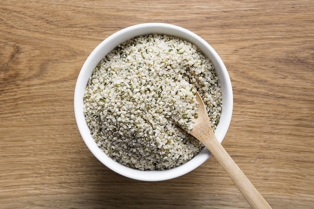 Grains de chanvre biologiques dans un bol sur une planche en bois.