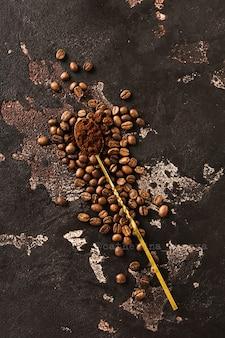 Grains entiers torréfiés frais de café arabica éparpillés et cuillère vintage avec du café moulu sur une vieille surface texturée marron