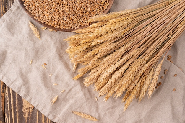 Grains et épis de blé sur une table en bois, vue de dessus avec espace de copie