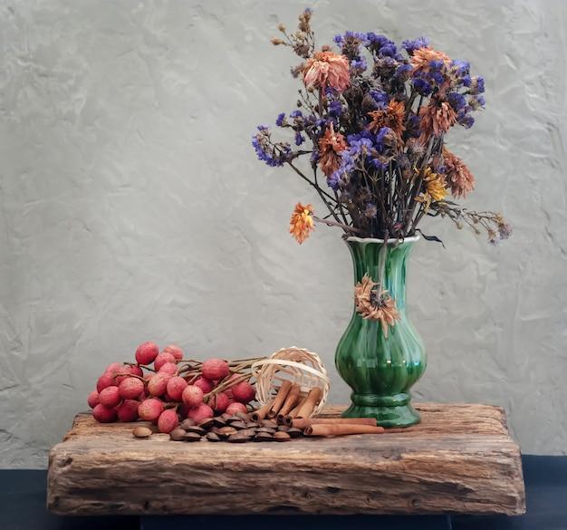 Grains et fleurs séchées dans un vase vert avec nature morte