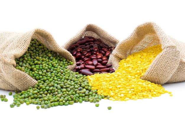Grains haricot mungo et haricots rouges dans un sac sur un blanc isolé