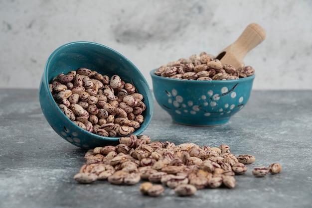 Grains de haricots crus affichés dans des bols.