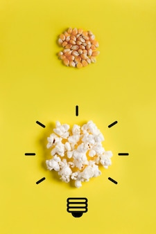 Grains de maïs et maïs soufflé avec dessin d'ampoule. concept d'évolution, d'idées, de remue-méninges, de processus créatif.