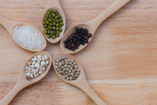 Grains placés sur 5 cuillères placées sur une table en bois