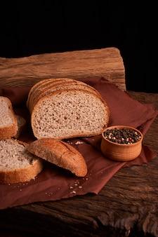 Grains de poivre dans un bol en bois sur une table avec un style rustique alimentaire. nourriture faite maison