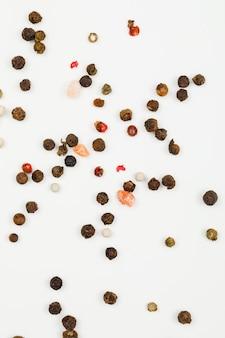 Grains de poivre mélangés sur blanc. mise à plat. verticale.