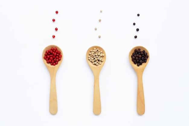 Grains de poivre noirs, rouges et blancs avec une cuillère en bois blanche