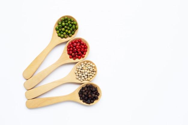 Grains de poivre vert, rouge blanc et noir avec une cuillère en bois sur blanc