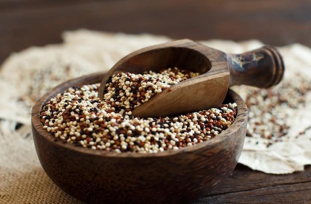 Grains de quinoa mélangés non cuits dans un bol avec une cuillère