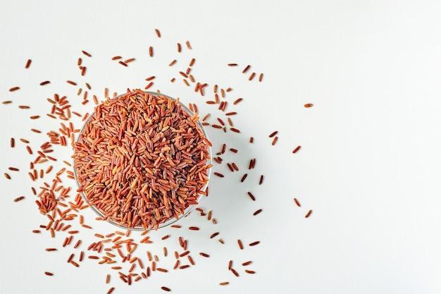 Grains de riz rouge cru dans une assiette en verre transparent