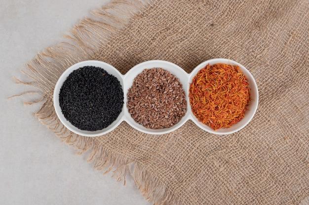 Grains de safran, de cumin et de blé dans des tasses blanches sur toile de jute.