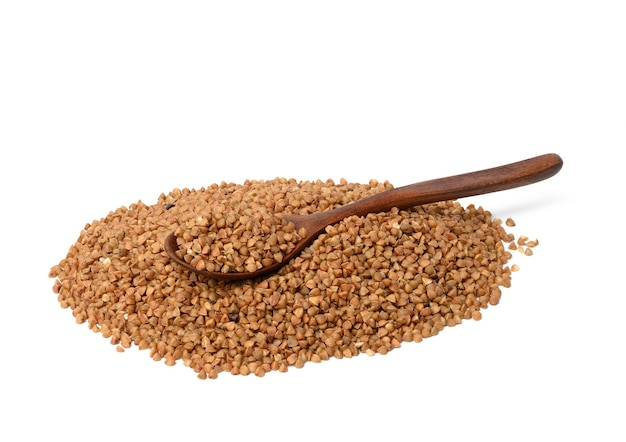 Grains de sarrasin crus dans une cuillère en bois isolé sur une surface blanche, gros plan