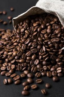 Grains torréfiés de café de bon goût renversés du sac
