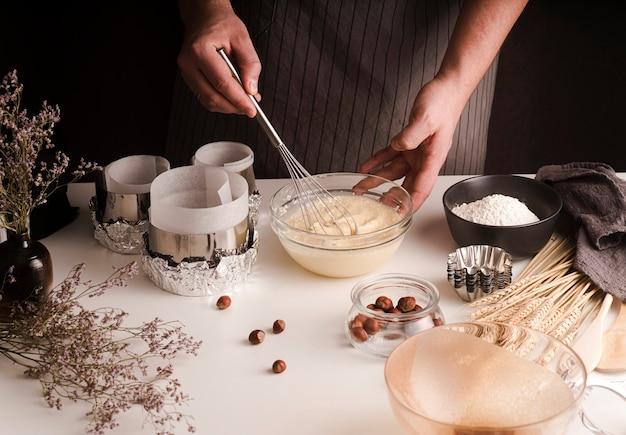 Grand angle de cuisson fouettant le mélange dans un bol