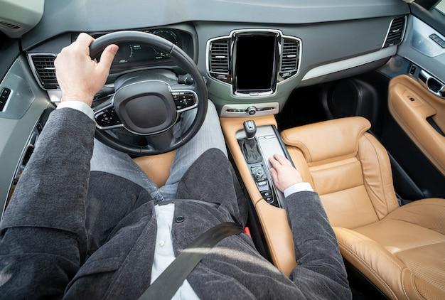 Grand angle drôle d'un conducteur masculin dans une voiture de luxe