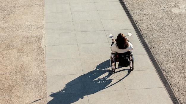 Grand angle, de, femme, dans, a, fauteuil roulant, dans rue
