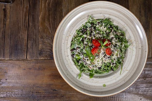 Ηgrand angle o salade avec tomates, tomates séchées au soleil, avocat, épinards, dinde et dessus de sésame