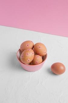 Grand angle d'oeufs de pâques décorés dans un bol sur la table