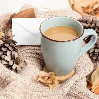 Grand angle de tasse de café avec des pommes de pin et des feuilles d'automne