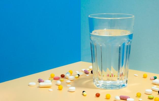 Grand angle de verre d'eau avec des pilules qui l'entourent