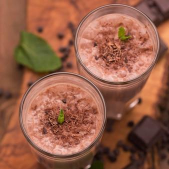 Grand angle de verres de milkshake avec du chocolat et de la menthe
