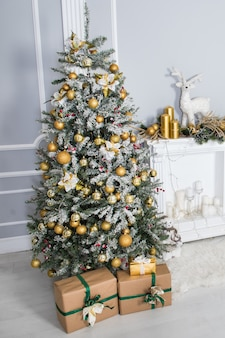 Grand arbre de noël avec des cadeaux dans une salle blanche