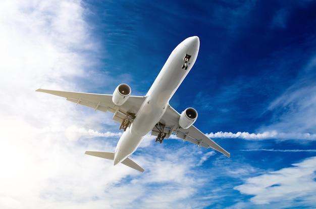 Grand avion de ligne blanc dans le ciel bleu.