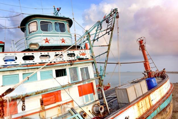 Grand bateau de pêche en bois s'arrêtant au port.